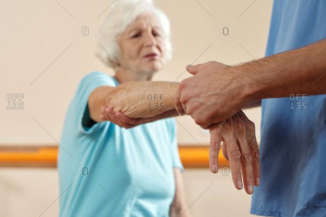 Unrecognizable physician exercising hand of defocused elderly Caucasian woman wincing at pain while getting physical therapy in recovery center