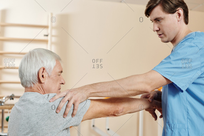 Professional male nursing assistant exercising hand of senior Caucasian man getting through physical therapy course in rehab center