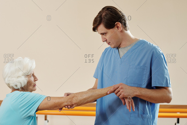 Professional male physiotherapist checking and exercising hand of senior Caucasian woman getting physical therapy in rehabilitation hospital