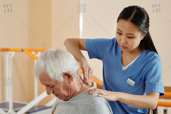 Young professional Asian nurse giving therapeutic massage to Caucasian elderly male patient in neurologic rehab hospital