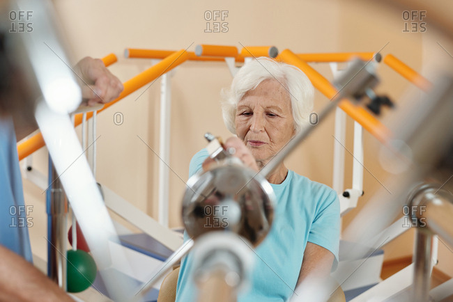 Elderly Caucasian woman doing exercises on training equipment while getting through physical therapy in neurological rehab clinic