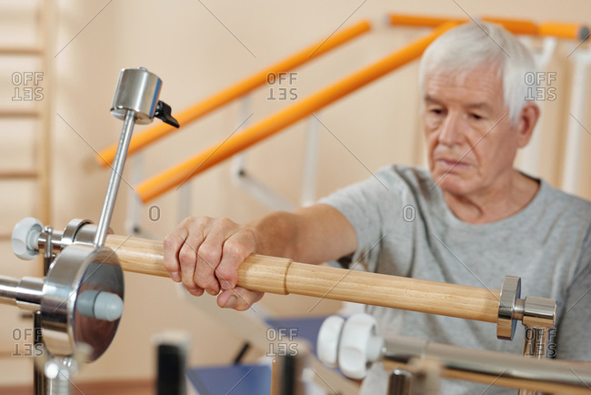 Senior Caucasian man doing exercises on rehabilitation equipment in hospital while getting through post-surgical physical therapy