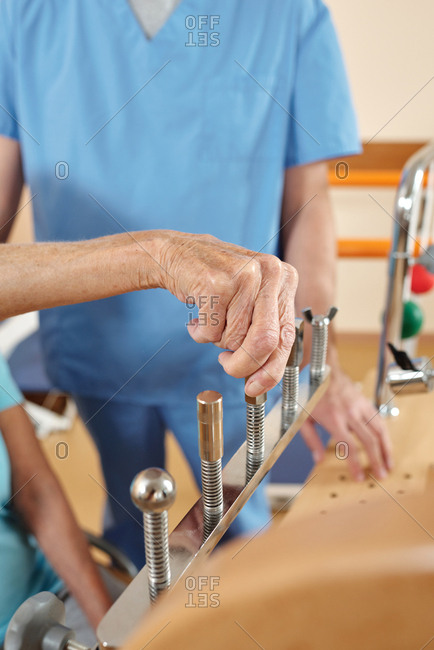 Close-up view of unrecognizable aged female patient training fine motor skills on rehab equipment in neurological hospital under control of nurse