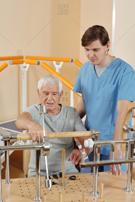 Elderly Caucasian man doing exercises on motor training equipment with professional male nurse while getting physical therapy in rehab center