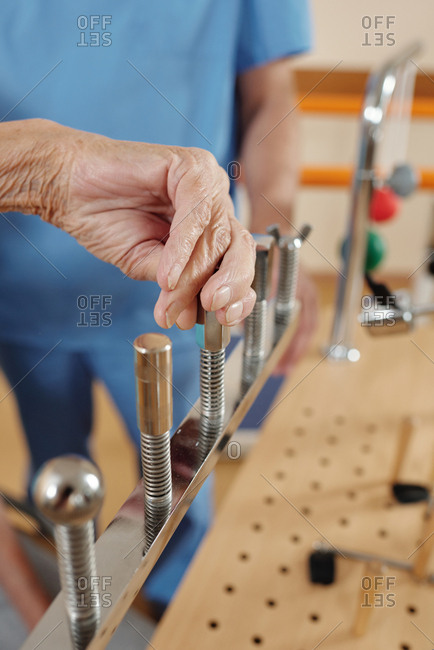 Close-up view of anonymous elderly woman exercising motor skills on training equipment in stroke rehab center under control of physiotherapist