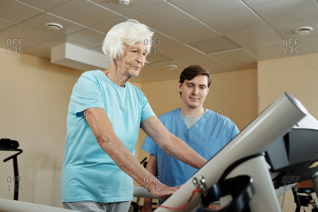 Elderly Caucasian woman walking on treadmill under control of nursing assistant while getting through physical therapy in rehab hospital