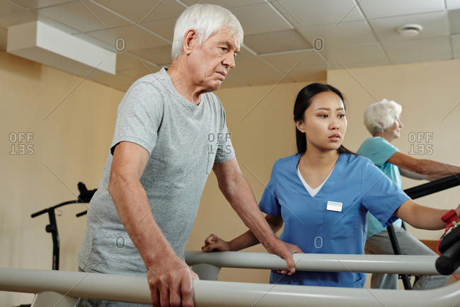 Aged Caucasian man walking on treadmill under control of young female nurse while getting through postsurgical physical therapy in rehab center