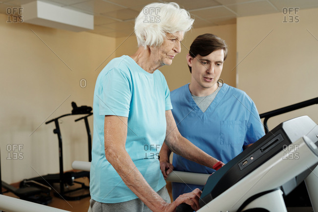 Senior Caucasian woman walking on treadmill under control of young male physiotherapist in gym of neurological hospital