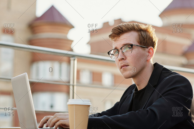 Young ginger-haired Caucasian man in glasses looking up thoughtfully while sitting at table in rooftop cafe and working on laptop