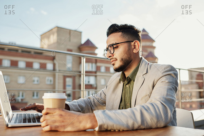 Profile portrait of young handsome Middle Eastern man in glasses sitting at table on rooftop terrace and working on laptop