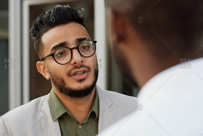 Waist-up portrait of young good-looking Middle Eastern bearded man in glasses  talking to unrecognizable male colleague outdoors