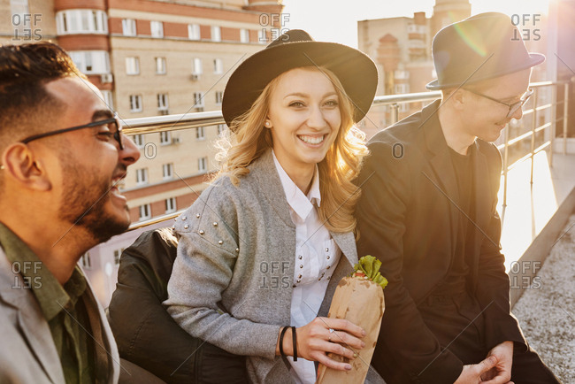 Group of young stylish friends sitting on rooftop terrace with snacks, chatting and enjoying evening, blond pretty woman smiling at camera