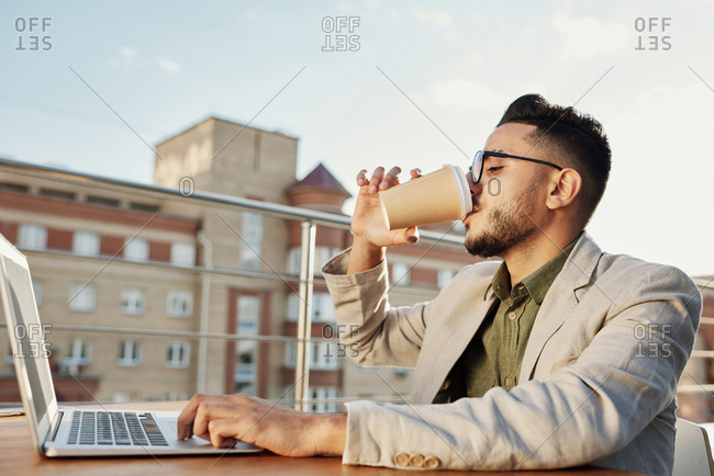 Young attractive Middle Eastern man wearing glasses drinking coffee from paper cup white sitting at table with laptop on rooftop cafe terrace