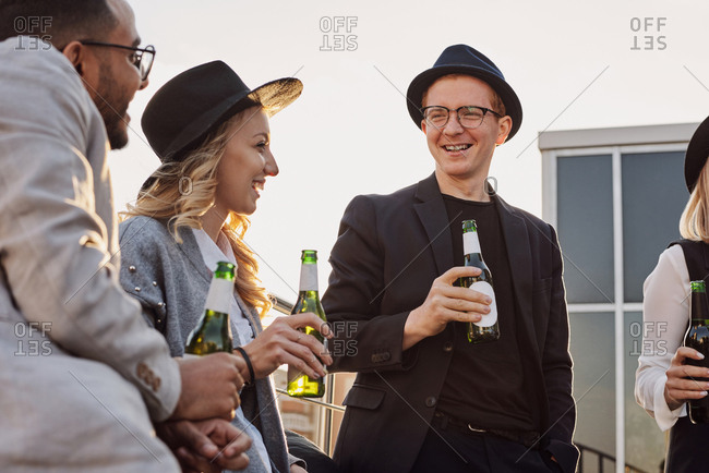 Multiethnic group of young fashionable people drinking beer, chatting and having a good time on rooftop terrace