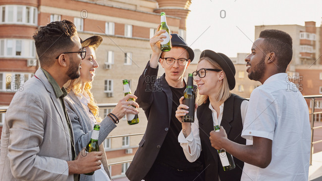 Multiethnic group of young trendy male and female colleagues drinking beer, talking and enjoying evening on rooftop terrace