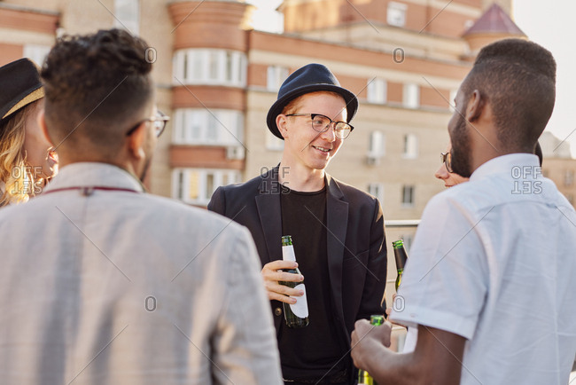 Multiethnic group of young stylish men and women standing on rooftop terrace, drinking beer and having friendly conversation