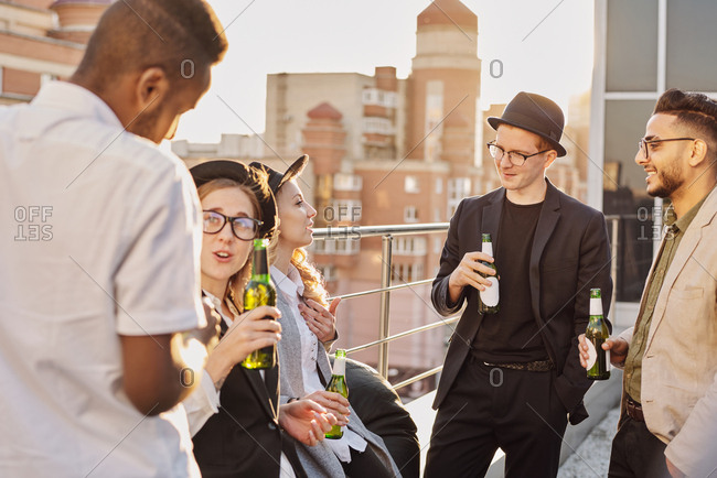 Multiethnic group of young fashionable male and female students standing on rooftop cafe terrace, chatting and drinking beer