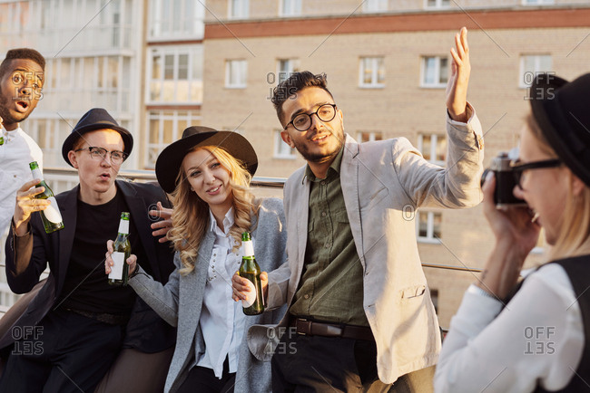 Photographer taking picture of multiethnic group of young stylish male and female coworkers hanging out on rooftop terrace with beer
