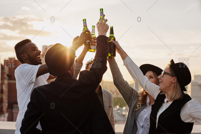 Multiethnic group of young male and female friends clinking bottles of beer and smiling cheerfully while hanging out on rooftop terrace