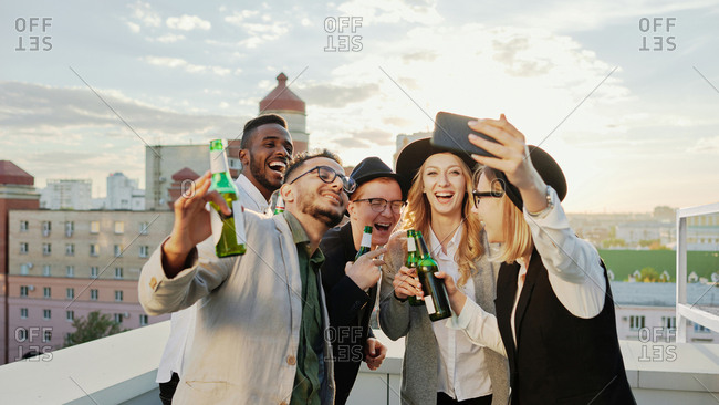 Multiethnic group of young male and female students taking selfie on smartphone and smiling happily while hanging out on rooftop