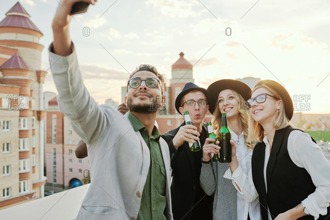 Multiethnic group of young stylish male and female friends taking selfie on smartphone while hanging out on rooftop terrace with beer