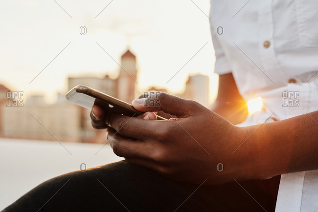 Close-up view of unrecognizable Black man texting on smartphone while sitting at sunset outdoors