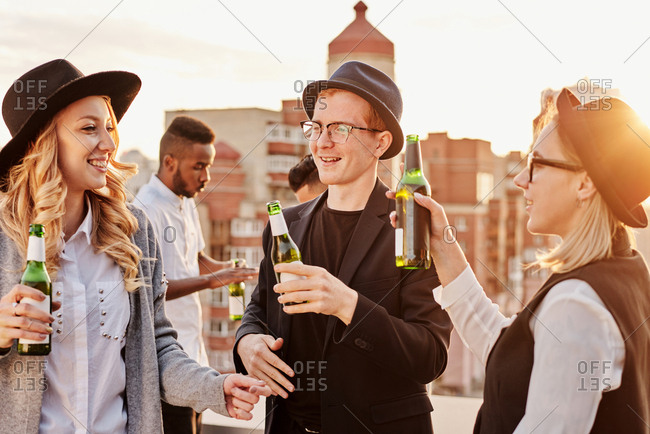 Multiethnic group of young stylish male and female coworkers hanging out on rooftop terrace at sunset, drinking beer and chatting