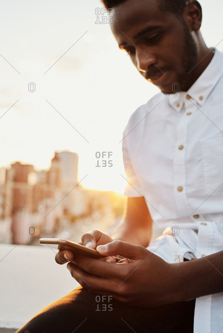 Portrait of defocused young handsome African American man texting on smartphone while sitting on rooftop terrace at sunset, low angle view