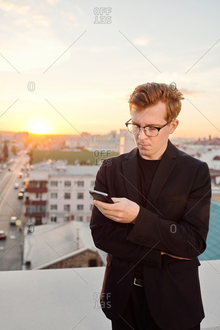 Portrait of young serious Caucasian man in black outfit and glasses using smartphone while standing on rooftop at sunset