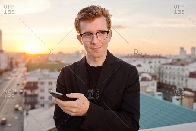 Waist-up portrait of young attractive red-haired Caucasian man standing on rooftop with smartphone and looking away thoughtfully