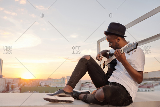 Young romantic Black man wearing casual clothes and hat playing the guitar while sitting alone on rooftop at sunset