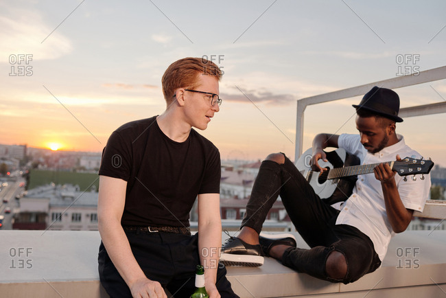 Young stylish ginger Caucasian man sitting on rooftop on summer evening and listening to his male African American friend playing the guitar
