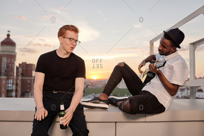 Young Black man playing the guitar and singing along with his ginger Caucasian male friend while spending summer evening with beer on rooftop
