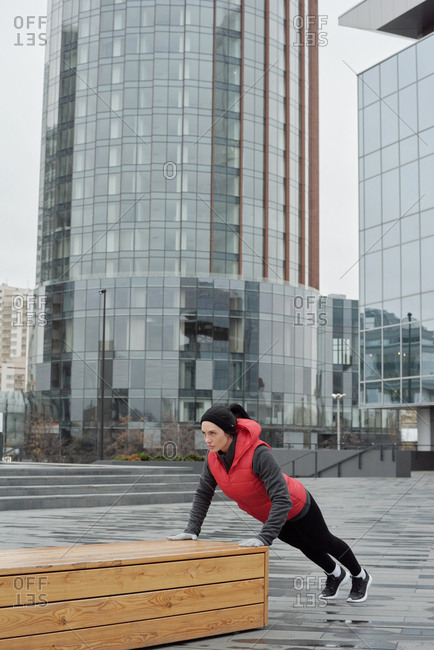 Young sporty Caucasian woman doing push-ups on wooden bench while having outdoor training in city center on cold autumn day
