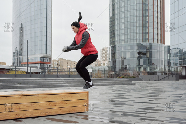 Determined young Caucasian woman doing jumping exercise while having outdoor workout in city center on cold gloomy morning
