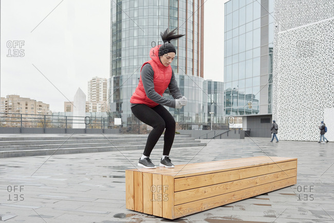 Young Caucasian woman in warm activewear doing bench jumps while having outdoor training in city center on cold autumn morning