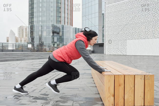 Young Caucasian female athlete warming up on wooden bench while having outdoor workout in central business district on cloudy autumn morning