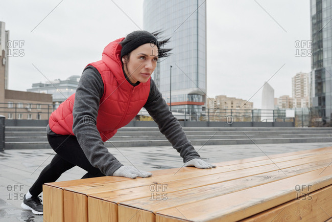 Portrait of young beautiful active woman doing warming-up exercise while having outdoor workout in downtown on cloudy autumn morning