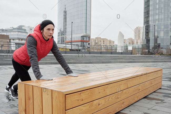 Young attractive Caucasian woman in warm sportswear doing exercises with wooden bench while having morning outdoor training in city center
