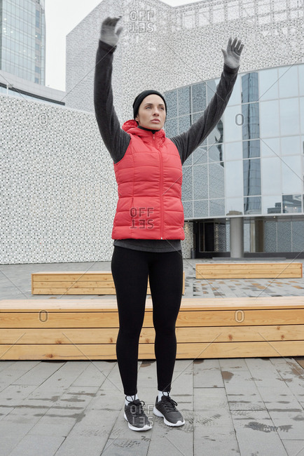 Young attractive Caucasian sportswoman doing warming up exercises before running while standing on background of modern business center outdoors