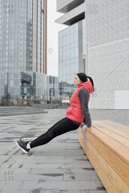Side view of young athletic Caucasian woman doing physical exercise on wooden bench in business district on cold autumn morning