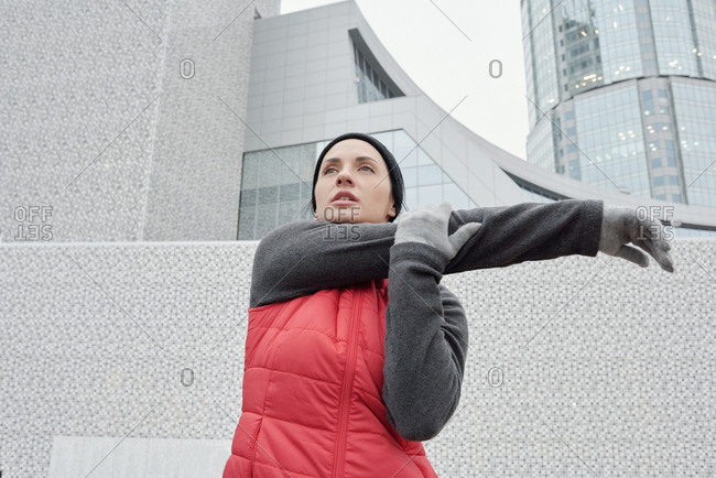 Low angle view of beautiful athletic Caucasian woman in warm sportswear doing physical exercises on background of modern office building
