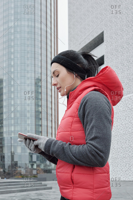 Low angle view of attractive Caucasian female runner using smartphone while having outdoor workout in downtown on cold autumn morning