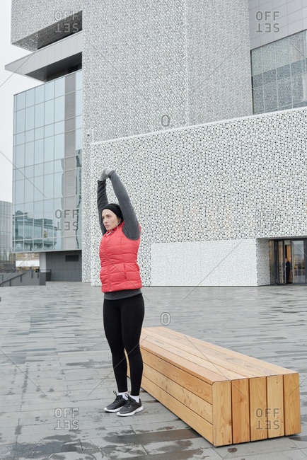 Young Caucasian woman in warm sportswear stretching while having morning outdoor workout on background of contemporary business center