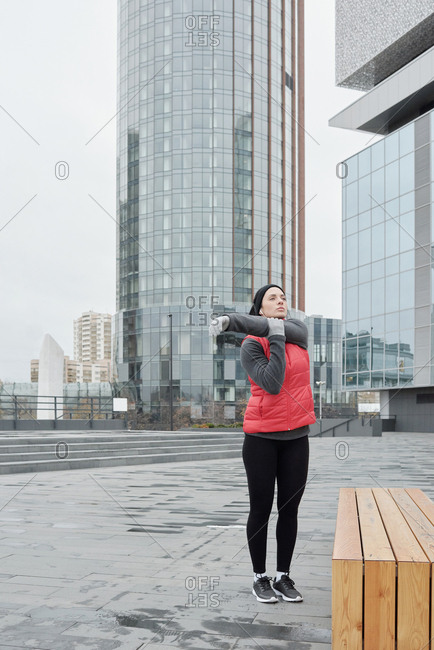 Young Caucasian sportswoman warming up while standing outdoors on background of modern office buildings on cloudy autumn morning