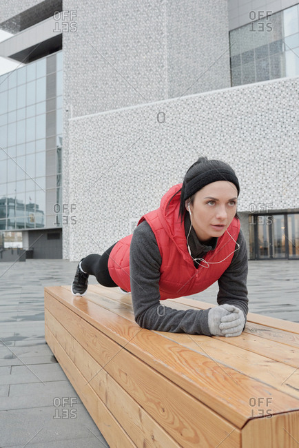 Young Caucasian sportswoman doing plank on wooden bench and listening to music while having outdoor workout in city center on cold autumn morning