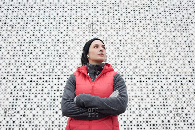 Portrait of young attractive female athlete standing outdoors against white perforated wall with crossed hands and looking up thoughtfully, low angle view
