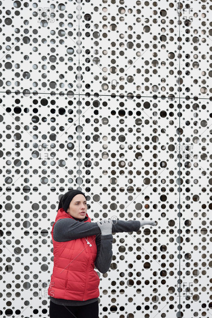 Young pretty Caucasian woman doing warming up exercise while standing outdoors against modern business center with perforated facade