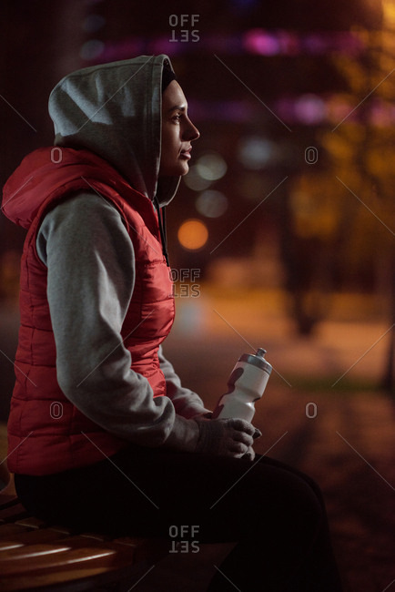 Woman resting after workout. Side view of female runner sitting on bench with sport bottle on autumn evening and looking into the distance on blurred background