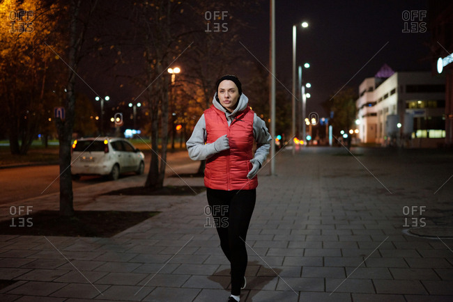Young attractive Caucasian woman in warm activewear running down the sidewalk while having outdoor workout on autumn evening